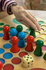 Hand mit Brettspiel und Würfel