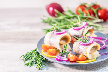 Delicious rolled herring fillet with red onion, cherry tomatoes, lemon and rosemary