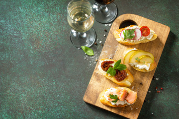 Italian Antipasti snacks set for Wine. Variety Brushetta with Soft Cheese, Pear, Radish, Salmon and Dried Tomatoes served on a rustic wooden board on a stone table. Copy space.