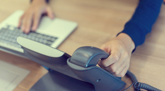 close up on employee man hand toucing on handset telephone with working on laptop at office desk concept