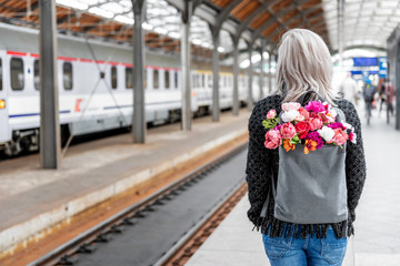 Blonde attractive woman with backpack with bouquet of flowers is waiting train. Photo from the back.