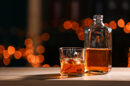 Glass and bottle of whiskey on wooden table against blurred lights