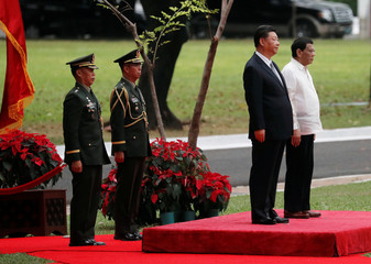 Visiting Chinese President Xi Jinping and Philippine President Rodrigo Duterte stand at attention during a welcoming ceremony for the Chinese leader at the Malacanang presidential palace in Manila