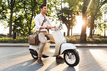 Young business man walking outdoors on scooter.