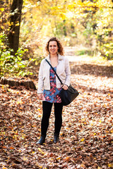 Curly woman standing on leaves between trees in a forest during an adventure on autumn