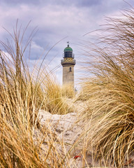 Lighthouse between dune grass. Rostock, Germany