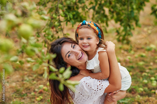 Happy family picking fresh organic fruits apples on farm. Smiling young family harvesting apples in summer garden. Harvest Concept.Greeting card for mother's day. Mother and daughter in apple orchard
