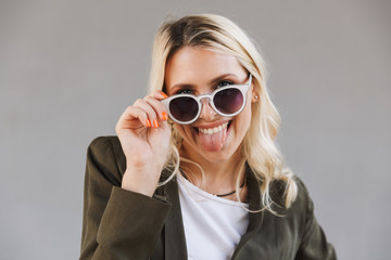 Image of cheerful woman 20s wearing stylish sunglasses showing her tongue at camera, isolated over gray background