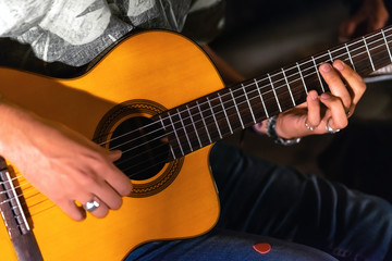 Man playing yellowe an acoustic guitar closeup