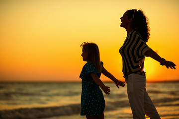 happy mother and daughter on seacoast at sunset rejoicing