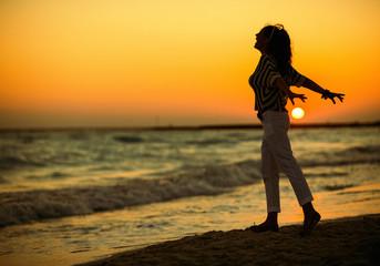 modern woman on beach at sunset rejoicing