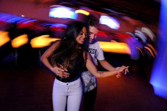 Pareja joven bailando salsa y bachata en una fiesta en club nocturno