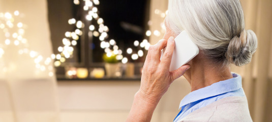 technology, communication, holidays and people concept - close up of senior woman with smartphone calling at home over garland lights background