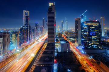 Beautiful aerial view to Dubai downtown city center lights skyline at night, United Arab Emirates. Long exposure light trails effect Fotobehang