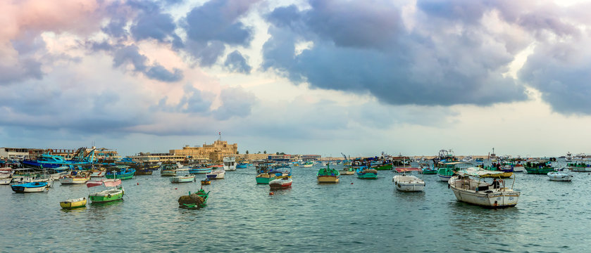 ALEXANDRIA, EGYPT - NOVEMBER 20, 2016: Cityscape with egyptian fisher boats, vessels and ships in the seaport at sunrise. Panoramic view with Qaitbay Citadel in a harbour of Alexandria.