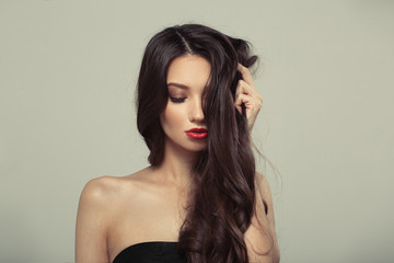 Fashion woman with curly shiny long hair. Gray background