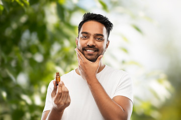 grooming and people concept - smiling young indian man applying lotion or beard oil over green natural background
