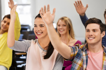 education, high school and people concept - group of smiling students raising hand in lecture hall