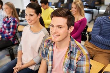 education, high school and people concept - group of smiling students in lecture hall