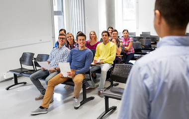 education, high school and people concept - group of smiling students with papers or tests and teacher at lecture hall