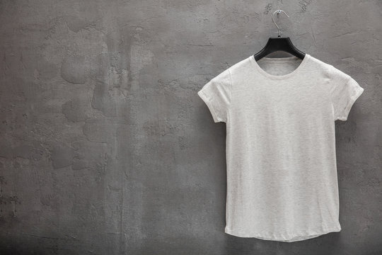 Front side of female grey melange cotton t-shirt on a hanger and a concrete wall in the background. T-shirt without print and copyspace for your text on left side