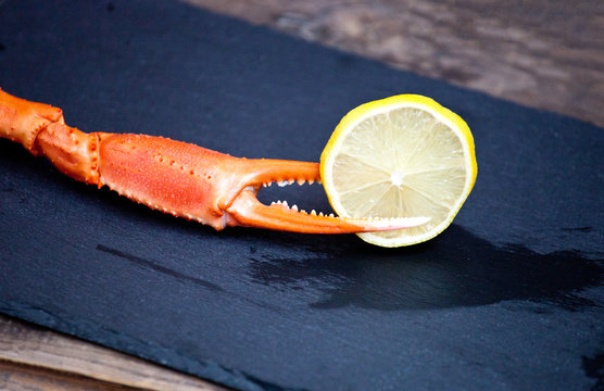 Snow crab claw with lemon on a table. Selective focus