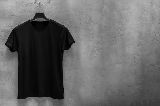 Front side of male black cotton t-shirt on a hanger and a concrete wall in the background. T-shirt without print and copyspace for your text on right side