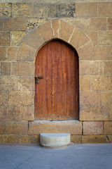 Old wooden door and window framed by arched bricks stone wall at the courtyard of al Razzaz historic house, Darb al Ahmar district, Old Cairo, Egypt
