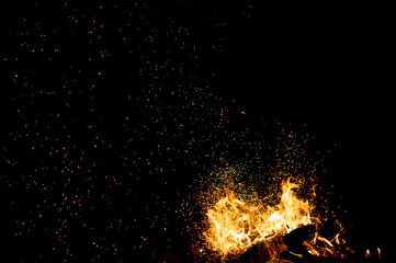 Burning woods with firesparks, flame and smoke. Strange weird odd elemental fiery figures on black background. Coal and ash. Abstract shapes at night. Bonfire outdoor on nature. Strenght of element.