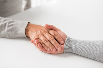 old age, family, care and support concept - close up of young woman holding senior man hands