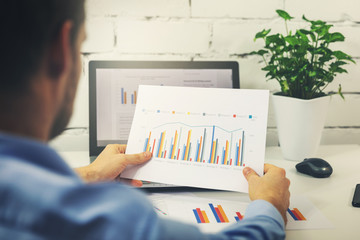 man working with business statistics data in office