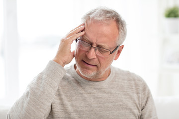 health care, stress, old age and people concept - senior man suffering from headache at home