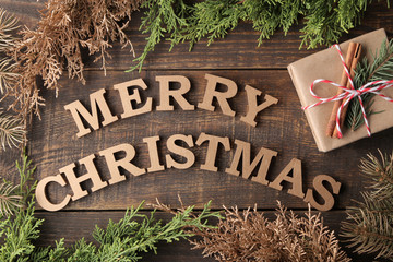 text merry christmas. gold letters and gift and christmas tree branches on brown wooden background. Top view of the new year. Christmas. holidays