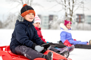 childhood, sledging and season concept - group of happy little kids sliding on sleds in winter