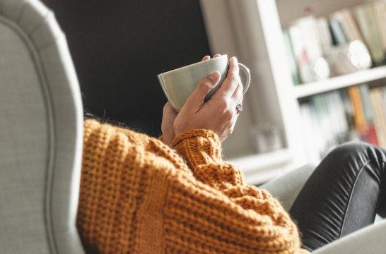 Junge Frau entspannt mit einer Tasse Tee im Sessel