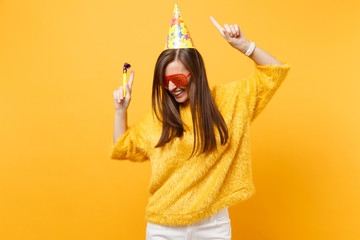 Joyful woman in orange funny glasses birthday party hat with playing pipe rising hands pointing index fingers up, dancing celebrating isolated on yellow background. People sincere emotions, lifestyle.