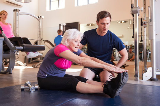 Senior Woman Exercising In Gym Being Encouraged By Personal Trainer