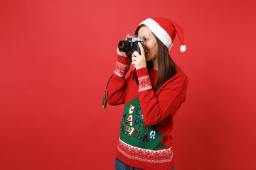 Attractive young Santa girl in Christmas hat taking pictures on retro vintage photo camera isolated on bright red background. Happy New Year 2019 celebration holiday party concept. Mock up copy space.