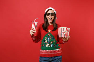 Excited young Santa girl in 3d imax glasses watching movie film holding popcorn, cup of soda isolated on red wall background. Happy New Year 2019 celebration holiday party concept. Mock up copy space.