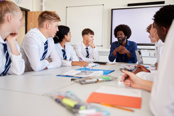 Male High School Teacher Sitting At Table With Teenage Pupils Wearing Uniform Teaching Lesson