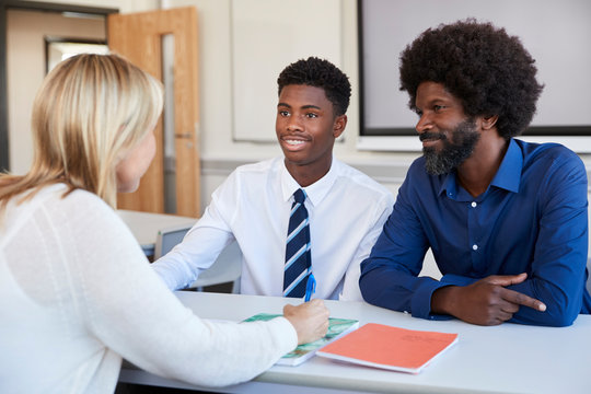 Father And Teenage Son Having Discussion With Female Teacher At High School Parents Evening