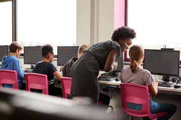 Female Teacher Supervising Line Of High School Students Working at Screens In Computer Class