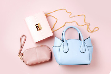 Fashion handbags on pale pink background. Flat lay, top view. Spring/summer fashion concept in pastel colored
