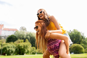 leisure, people and friendship concept - happy teenage girls or friends having fun at summer park