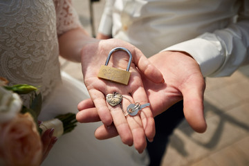 Wedding padlock on hand of bride and groom close up