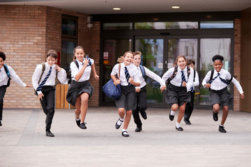 Group Of High School Students Wearing Uniform Running Out Of School Buildings Towards Camera At The End Of Class