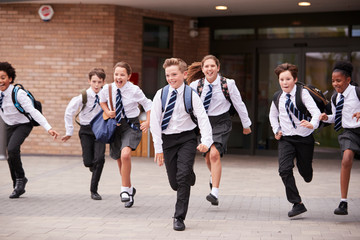 Group Of High School Students Wearing Uniform Running Out Of School Buildings Towards Camera At The End Of Class Fototapete
