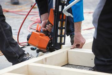 Professional carpenter using pneumatic nail gun