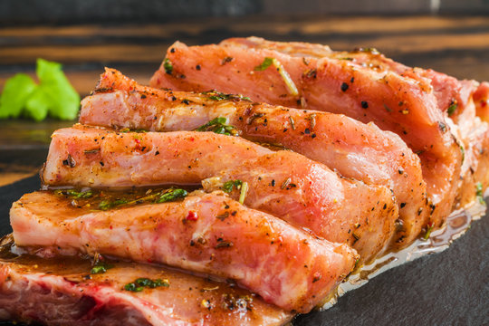 Raw pork fillet marinated with pepper, salt, fresh parsley, honey, paprika, cumin on black stone board