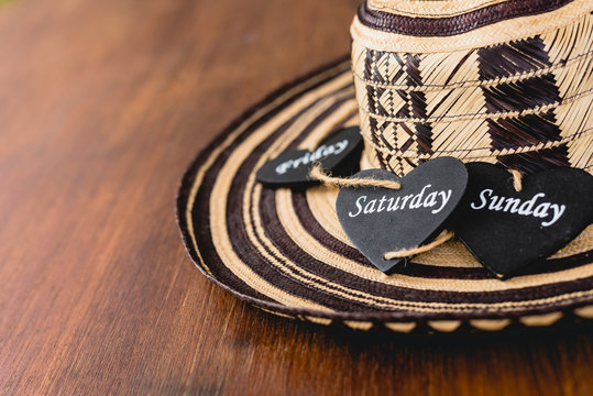 Black wooden heart with name of weekend days over a Mexican hat.